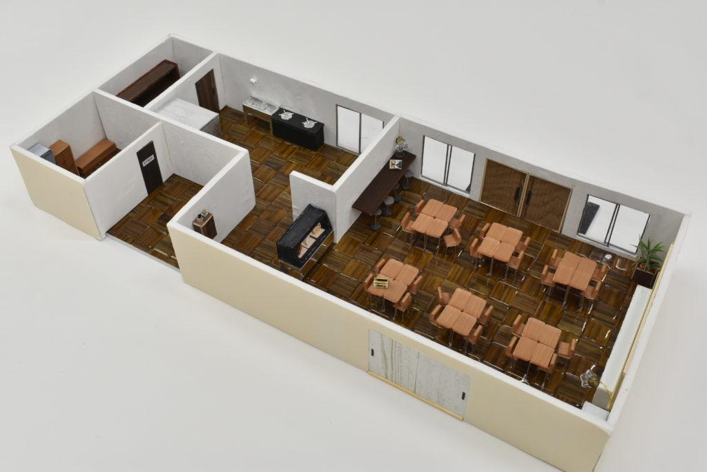 模型全体です。カフェスペース全体のインテリアは、教室の要素を残しています。 厨房やスタッフルームには防災設備や防災用具を収納できるスペースがあります。