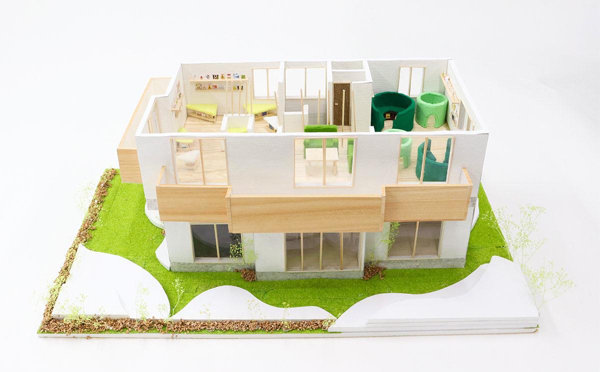 建物全体模型:屋根を取り外しした状態です。芝生の緑色と外壁の白色のコントラストが映え、家具や窓枠が茶色で自然でリラックスできる雰囲気を醸し出しています。